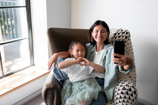 Woman having a video call with her husband next to their daughter