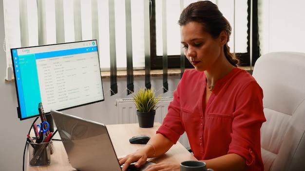 早朝に職場でラップトップでビデオ会議をしている女性。ビジネスリモートチームと協力してチャットを話し合うフリーランサー、オンライン会議、インターネットテクノロジーに関するウェビナー