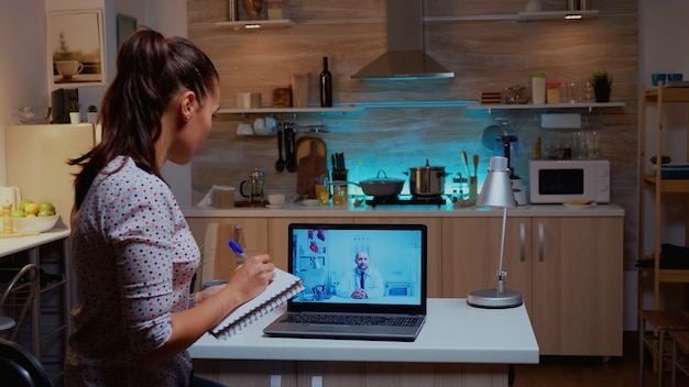 Woman having a video conference with doctor late at night and taking notes. physician giving consultation to sick patient from hospital office during virtual examination, device, medicine, appointment