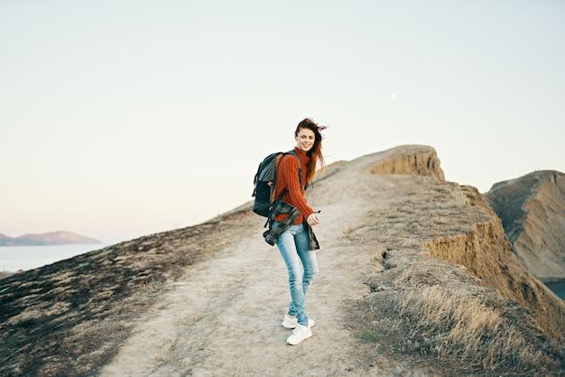 海の後ろの景色の近くの道路に沿って山に向かっている女性
