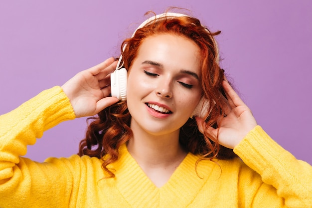 La donna in cuffia si gode le sue canzoni preferite sul muro lilla