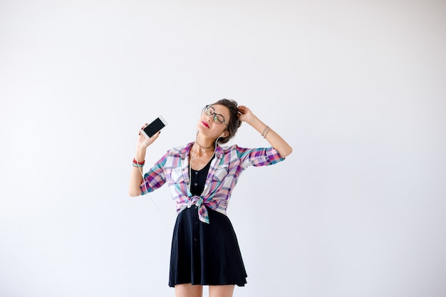 Woman in headphones and glasses listening to music and dancing