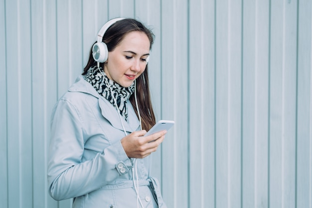 Woman in headphones and in a gray coat looks at a smartphone