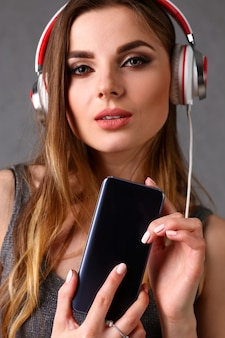Woman in headphones holding smartphone in hand.