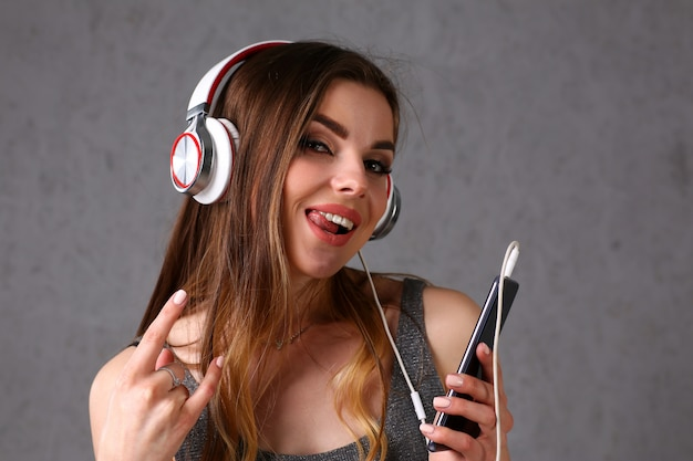 Woman in headphones holding smartphone
