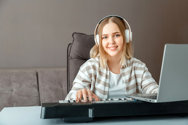 Woman in headphones learn to play piano online using laptop at home interior. woman play synthesizer piano during online lesson with teacher.teenager girl record online concert stream performer.