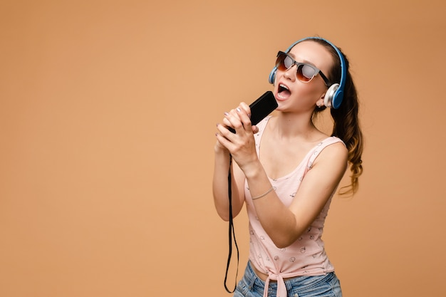 Woman in headphones listening to music and singing