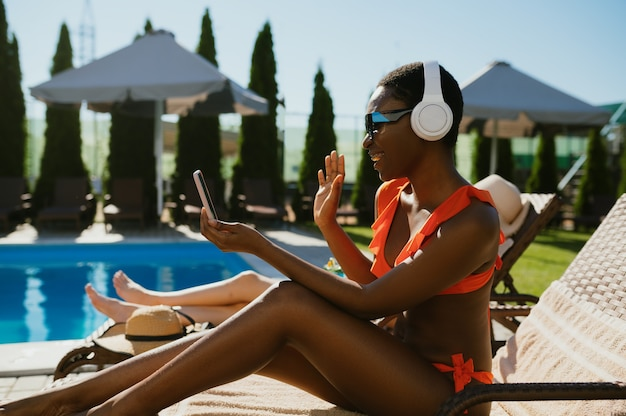 Woman in headphones listening to music on sun bed