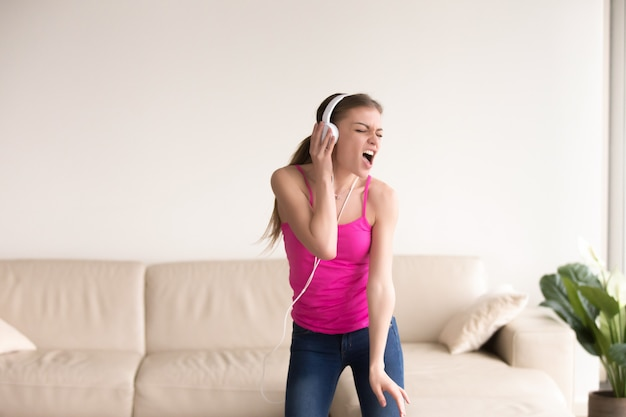 Woman in headphones singing and dancing at home