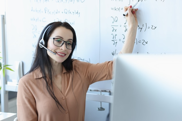 Woman in headphones sitting in front of laptop and showing information on whiteboard