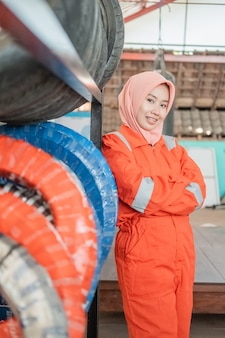 Woman in a headscarf wearing a wearpack uniform with crossed hands next to a tire rack in a motorcycle repair shop