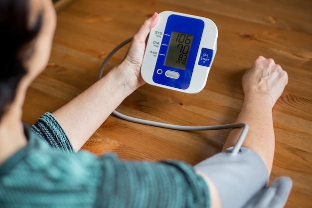 女性の健康は、デジタル圧力、健康と医療の概念で自宅で血圧と心拍数をチェックします