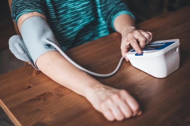 Здоровье женщины проверяет артериальное давление и частоту сердечных сокращений дома с помощью цифрового давления, здоровья и медицинской концепции