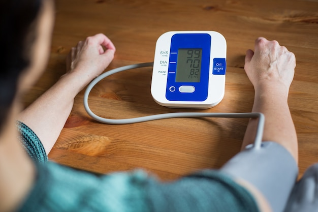 Woman health check blood pressure and heart rate at home with digital pressure, health and medical concept