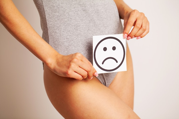 Woman health, female body holding sad smile card near stomach.