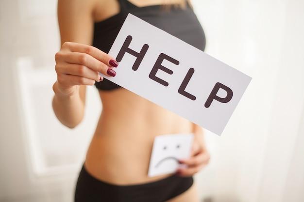 Woman health. female body holding symbol help card near stomach