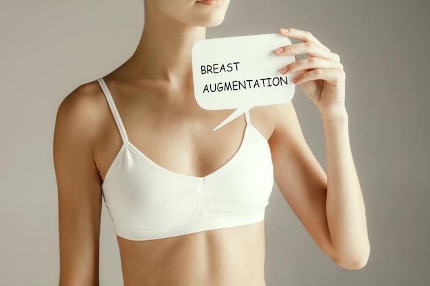 Здоровье женщины. женская модель держит карту со словами увеличение груди. молодая взрослая девушка с бумагой для знака или символа, изолированных на сером фоне студии. медицинская проблема и решение.