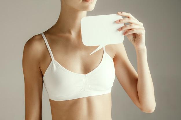 女性の健康。胸の近くに空のカードを持つ女性モデル。灰色のスタジオの背景に分離された記号または記号の紙を持つ若い大人の女の子。胴体の一部を切り取ります。医療上の問題と解決策。