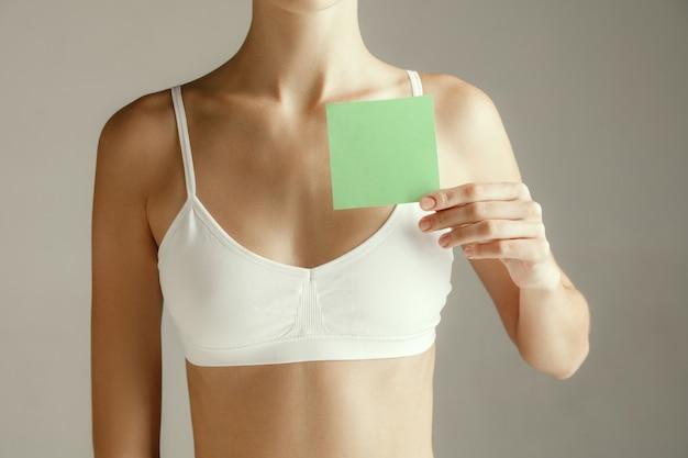 女性の健康。胸の近くに空のカードを持つ女性モデル。灰色のスタジオの背景に分離された記号または記号の紙を持つ若い大人の女の子。胴体の一部を切り取ります。医療上の問題と解決策。 Premium写真