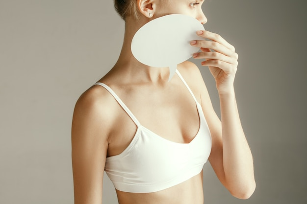 Woman health. female model holding empty card near breast. young adult girl with paper for sign or symbol isolated on gray studio background. cut out part of body. medical problem and solution.