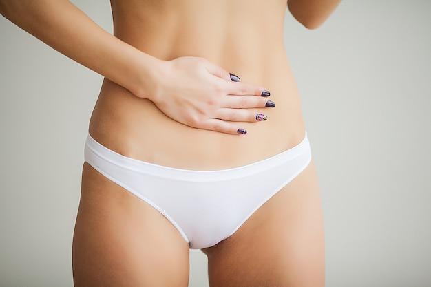 女性の健康問題。彼女の胃の近くの悲しいスマイリーの顔で白いカードを保持しているパンティーでフィットのスリムなボディを持つ女性のクローズアップ。