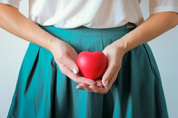 Woman healthcare and gynecology concept. a woman's hands holding a heart symbol on belly