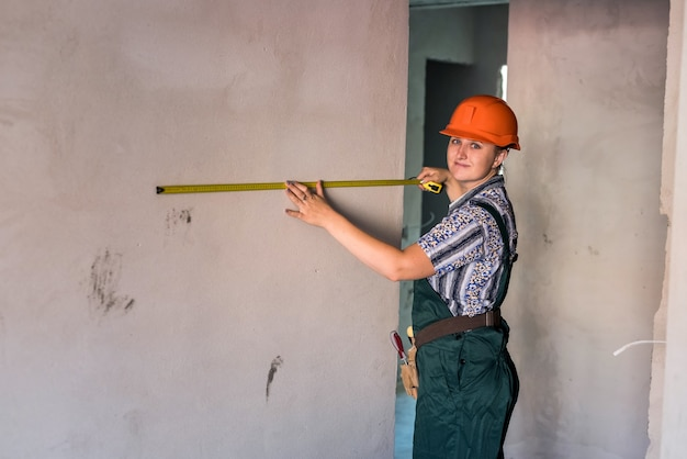 Woman in helmet and protective uniform posing with meter
