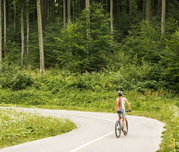Woman in helmet riding on mountain bicycle.