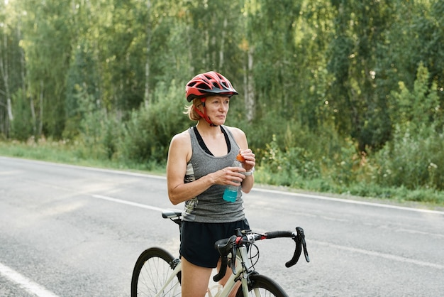 Woman in helmet standing on the road and drinking water after her training on the bike
