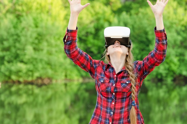 Woman in the helmet of virtual reality outdoor
