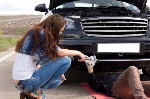 그녀의 차를 수리하는 정비공을 돕는 여자