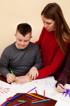 Woman helping boy with down syndrome draw