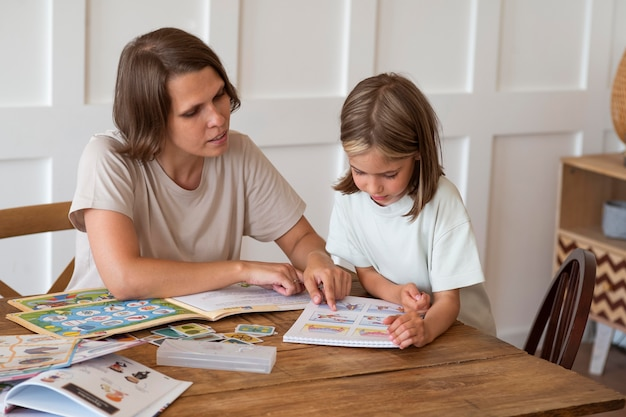 ミディアムショットを勉強する女の子を助ける女性