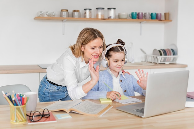 Woman helping her daughter study at home