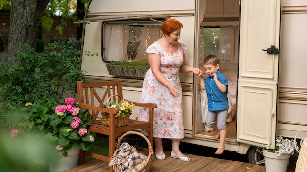 Женщина помогает своему внуку спуститься с каравана