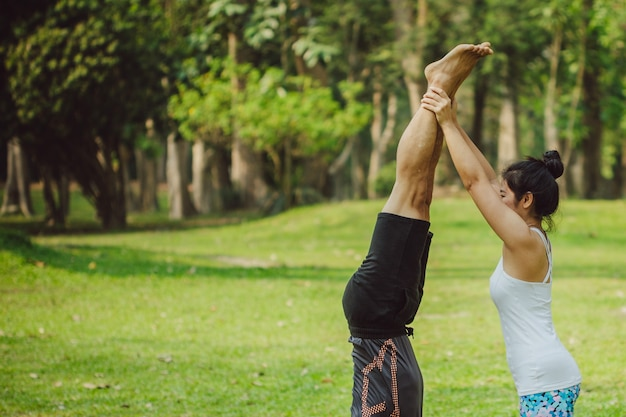 Woman helping her partner to handstand
