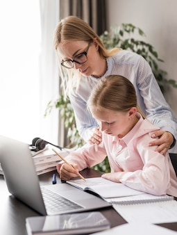 Donna che aiuta una bambina a fare i compiti