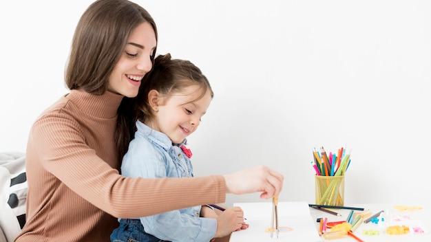 Женщина помогает маленькой девочке рисовать