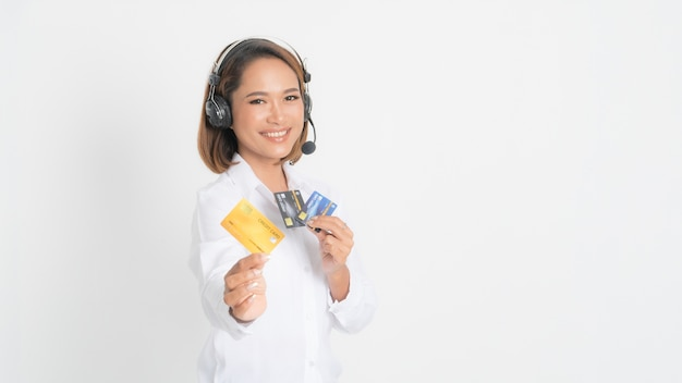 Woman helpline operator or call center showing blank credit card, headset holding her arms crossed isolated on white.