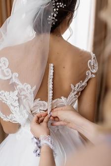 여자는 신부의 웨딩 드레스에 버튼을 고정하는 데 도움이