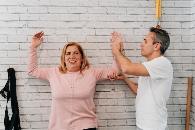 Woman in her 60s doing arm exercises with a personal trainer to help with muscle pain after injury