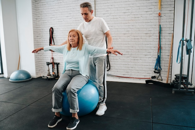 Woman in her 70s being assisted by a physio in her 40s to regain full arm mobility