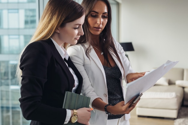 Woman and her assistant holding documents discussing business plan and strategy at workplace.