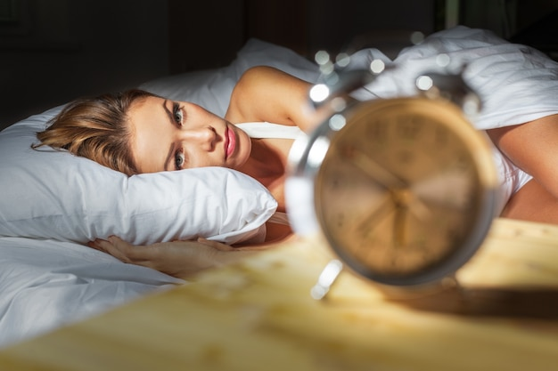 Woman  in her bed with insomnia and nightmares can't sleep waiting for her alarm clock to go off