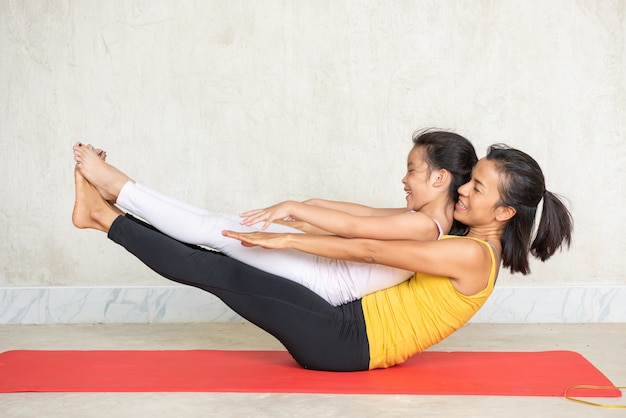 Woman and her charming little daughter doing yoga