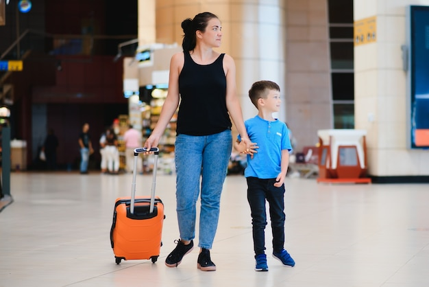 Woman and her child passing through the airport terminal