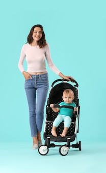 Woman and her cute baby in stroller on color surface