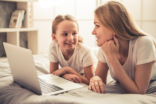 Woman and her cute little daughter are using a laptop.