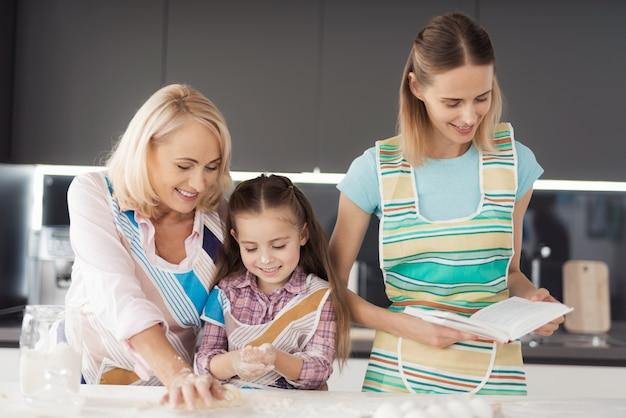 여자 그녀의 딸과 할머니는 홈 메이드 비스킷을 준비합니다.