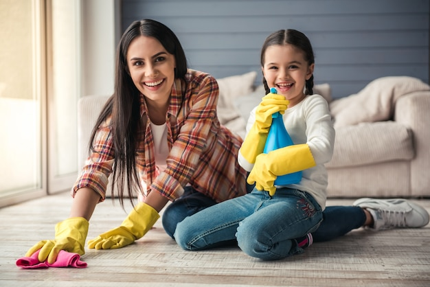 Woman and her daughter are smiling while cleaning floor.
